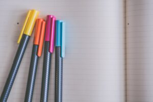 yellow-orange-pink-and-blue-coloring-pens-on-white-notebook-998591